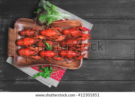 Cancers to beer, dill, boiled crawfish, beer snacks, green leaves of fresh lettuce, parsley on a wooden tray on a black dark wooden background, top view, empty place for text, recipe - stock photo