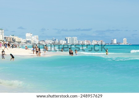 CANCUN - JANUARY 18: Tourists enjoy the sunny weather and relaxing on the beautiful beach on 18 January 2015 in Cancun, Mexico. This is one of the best beaches in the Mexico. - stock photo