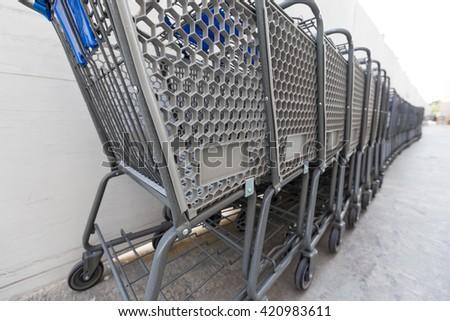 Cancun, Mexico - 9 February 2016: Shopping cart near Walmart supermarket. Closeup on shop trolley with sign Walmart - stock photo