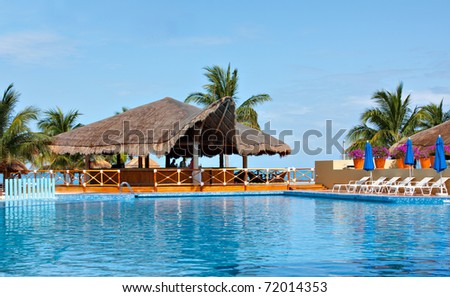 Cancun swimming pool and palapa overlooks ocean. - stock photo