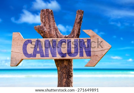 Cancun wooden sign with beach background - stock photo