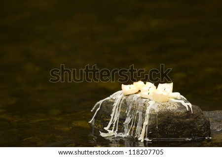 Candels sitting on rock with christmas decorations near stream - stock photo