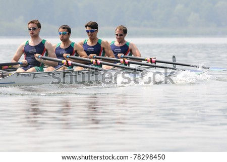 CANDIA, TURIN, ITALY - MAY 22: the CUS Milano quad (quadruple) scull (4x) crew rowing during 2011 Rowing CNU University National Championship on May 22, 2011 on Candia lake, Turin, Italy - stock photo