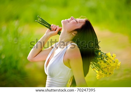 candid adorable girl in white dress is carefree with flowers in green field during spring. - stock photo