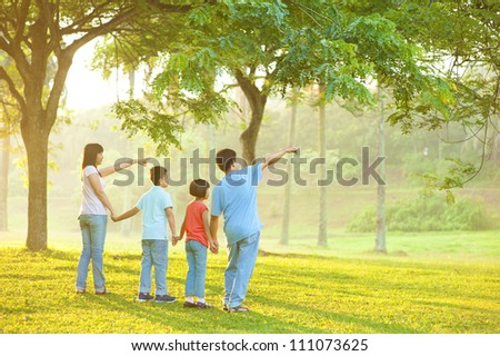 Candid Asian family pointing at outdoor park - stock photo