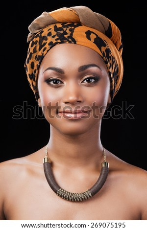 Candid beauty. Portrait of beautiful African woman wearing headscarf and smiling while looking at camera and standing against black background - stock photo