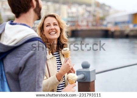 candid couple eating icecream on date having fun smiling - stock photo