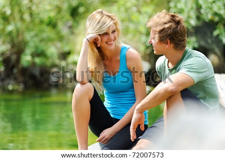 candid couple having fun outdoors, carefree summer romance concept - stock photo