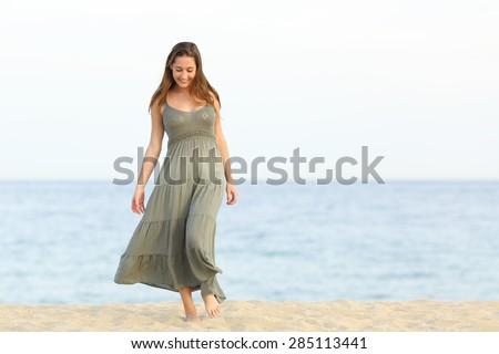 Candid feminine longing girl walking enjoying carefree on the sand of the beach towards camera - stock photo