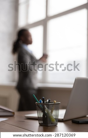Candid image of a businesswoman drinking coffee while working at office. Selective focus. - stock photo