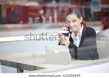 Candid image of a businesswoman talking on the phone in a cafe