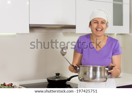 Candid image of an attractive laughing female cook in and apron and toque holding a big metal saucepan - stock photo