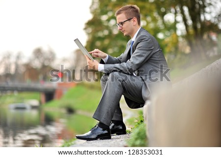 Candid image of young businessman sits using Tablet Computer near the river - stock photo