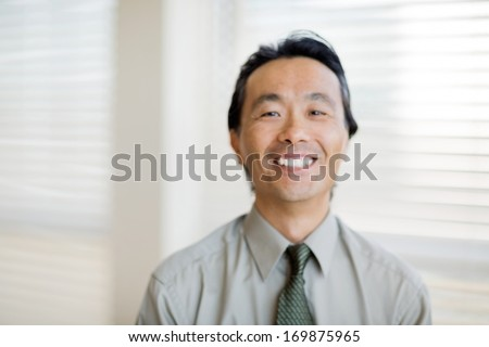 Candid out of focus shot of happy smiling doctor near window - stock photo