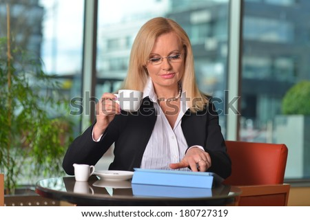 Candid photo of a attractive middle-aged blond businesswoman working at hotel lobby with a tablet pc/smart-phone and drinking coffee  - stock photo