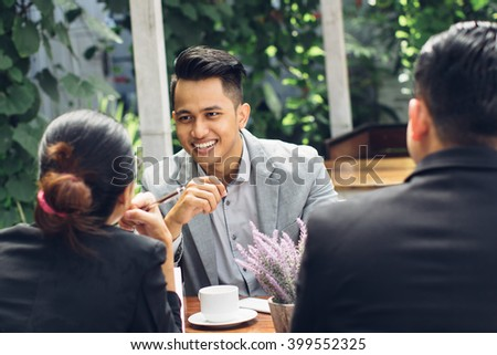 candid portrait of a confident businessman meeting at cafe with his team - stock photo
