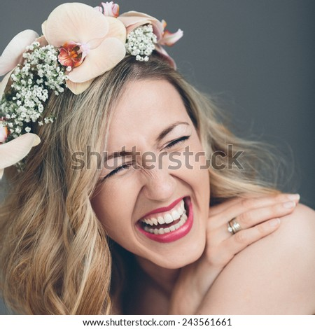 Candid portrait of a gorgeous laughing vivacious bride with long blond hair wearing a headband of pink orchids, close up head shot