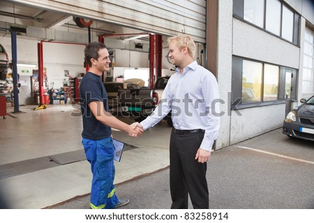 Candid portrait of a mechanic shaking hands with client - stock photo