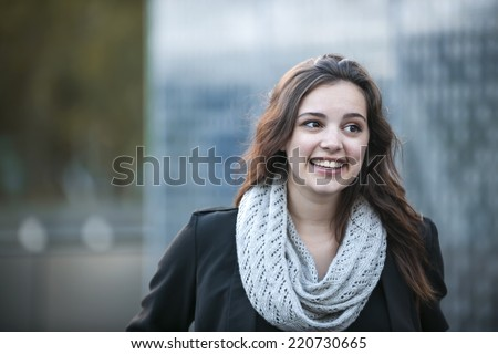 Candid portrait of happy young brunette woman smiling with copy space in urban setting - stock photo