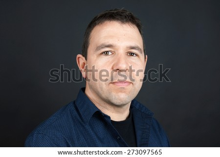 Candid portrait of man with neutral facial expression - stock photo