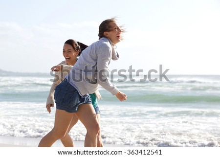 Candid portrait of two women laughing at the beach - stock photo