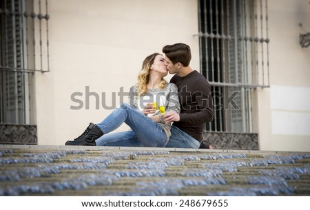 candid portrait of young beautiful couple in love sitting on street together celebrating Valentines day with Champagne toast on casual clothes and urban background - stock photo