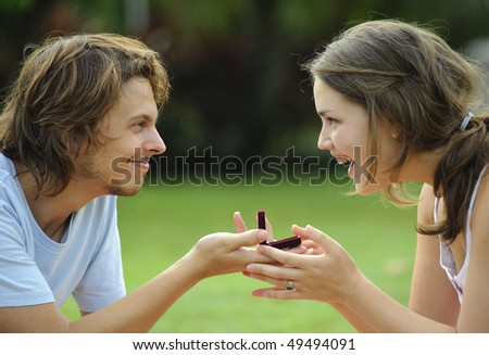 Candid proposal outdoor in the park, attractive couple - stock photo