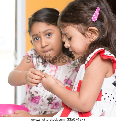 Candid shot of Indian girls sharing traditional snack murukku with each other. Asian sibling or children eating food, living lifestyle at home. - stock photo