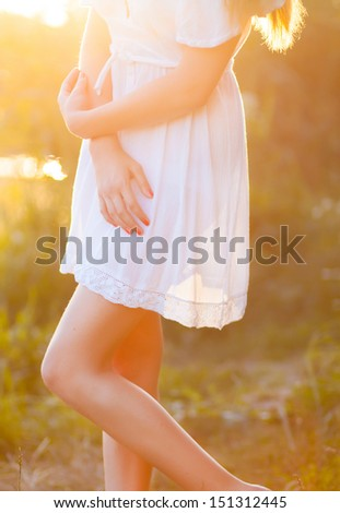 Candid skipping carefree adorable woman in field at summer sunset. - stock photo