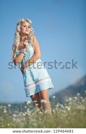 Candid skipping carefree adorable woman in field with flowers. - stock photo