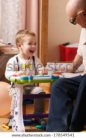 Candid spontaneous portrait of a beautiful laughing toddler sitting at a small table in his bedroom playing with his grandfather - stock photo