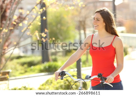 Candid woman walking in an urban park in summer or spring carrying a bicycle - stock photo