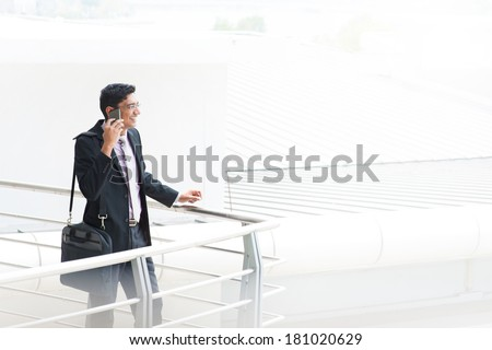 Candid young Asian Indian businessman on the phone at outdoor building. India male business man, real modern office building as background. - stock photo