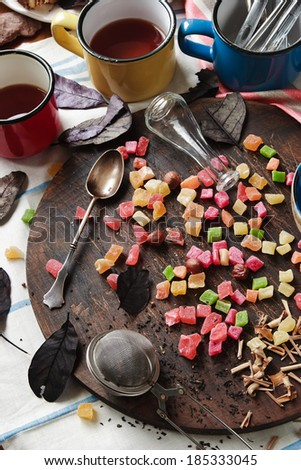 Candied fruit on the black round board and cups of tea - stock photo