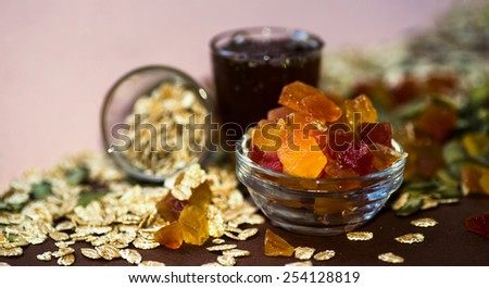 Candied papaya in small blue bowl, cereals oatmeal, spelled, pumpkin seeds and honey on pink and dark red background, nice lighting, vivid colors - stock photo