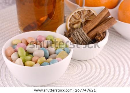 candies and tea cup, cinnamon, lemon, fruits - stock photo