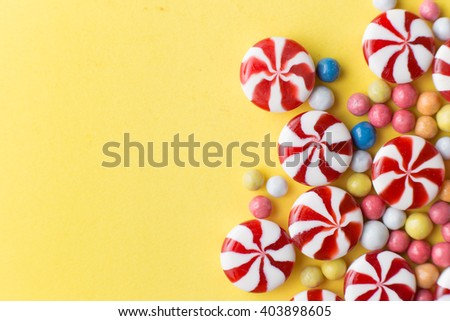 Candies colorful mix on yellow bright background with copy space top view. - stock photo