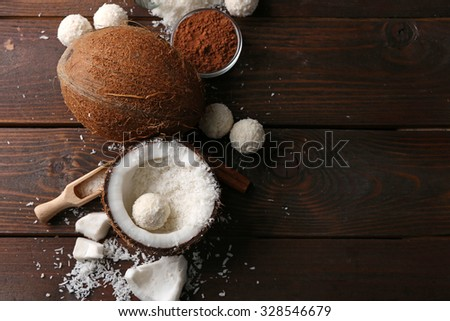 Candies in coconut flakes and ingredients on dark wooden background - stock photo