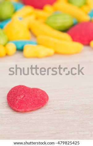 Candies with different shapes and colors on a gray wooden background