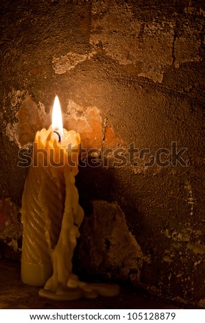 candle against a brick wall - stock photo