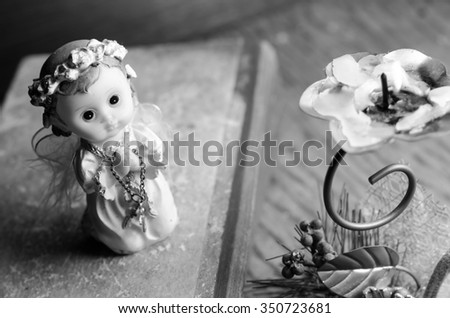 candle and angels on wooden background, horizontal photo