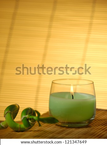 Candle and bamboo laying on matte - stock photo