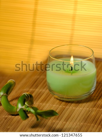 Candle and bamboo laying on matte different angle - stock photo