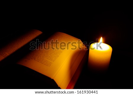 Candle and book in Candlelight - stock photo