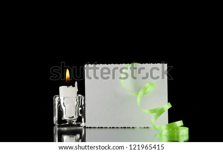 candle and business card on a black background - stock photo
