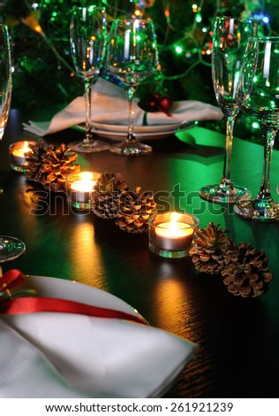 Candle and cones as an element of decor Christmas table - stock photo