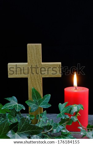 Candle and cross on slate with ivy. Holy symbols for Christian celebrations such as Easter - stock photo
