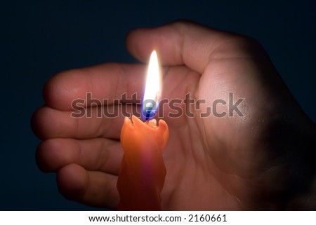 Candle and hand in darkness