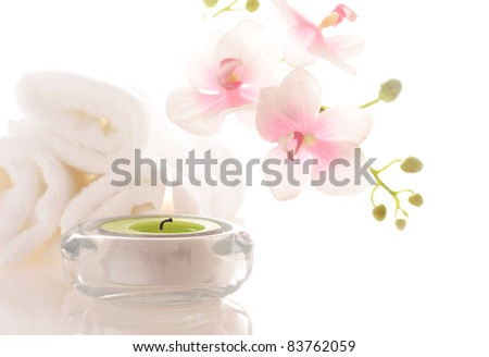 candle and massage stones on white background - stock photo