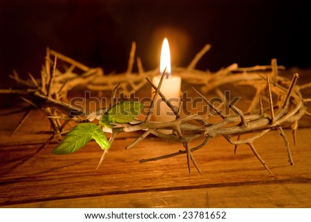 Candle burning in the middle of a crown of thorns at easter - stock photo
